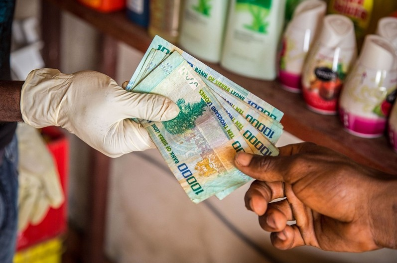 Michael Duff AP Photo of gloved hand handing over Leone currency