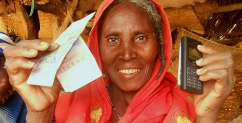 Lady holding cash transfers re-loadable card and a telephone