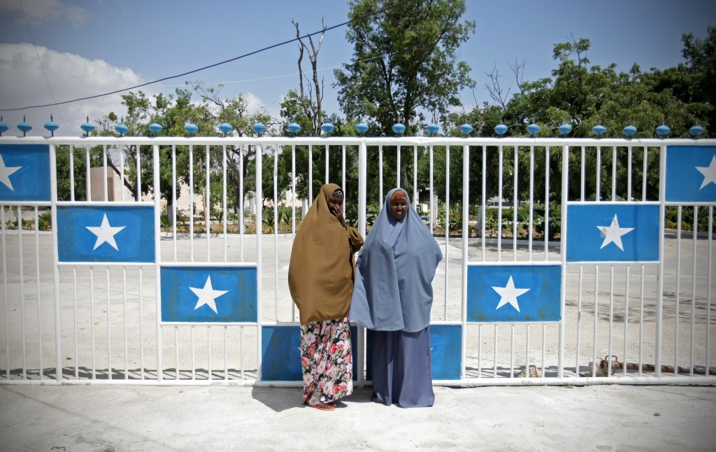 Two women stand at a gate adorned with the Somali national colours inside Villa Somalia (Credit: Stuart Price)