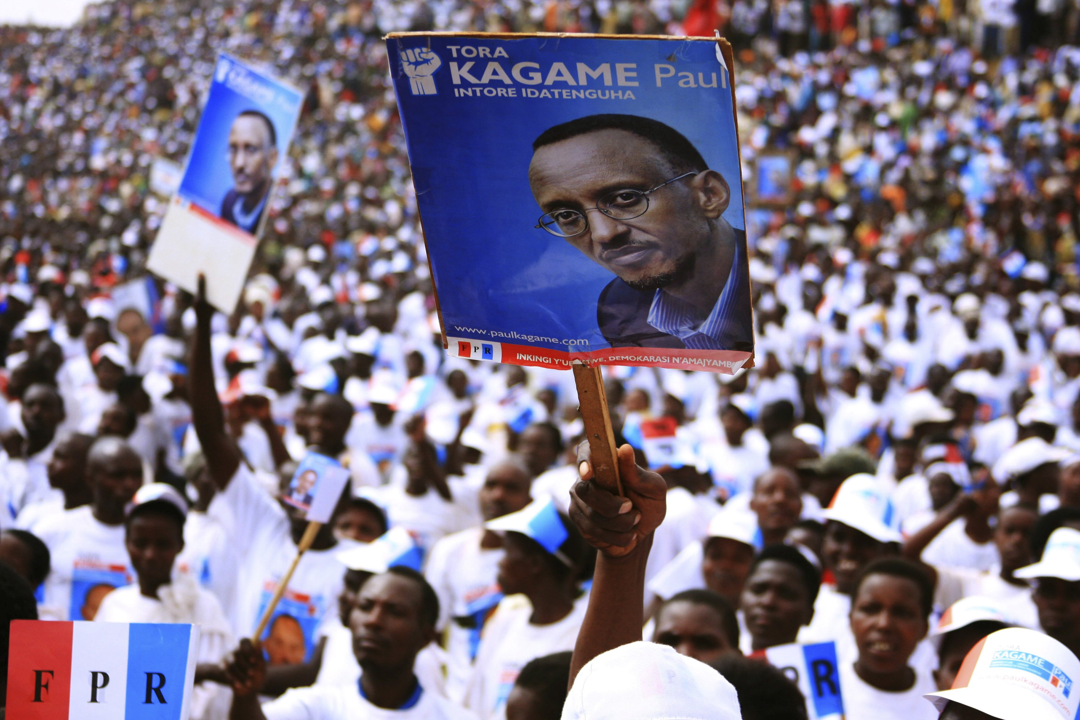 Supporters of the ruling Rwandan Patriotic Front hold posters of incumbent President Paul Kagame at a rally ahead of the country's presidential election in ...